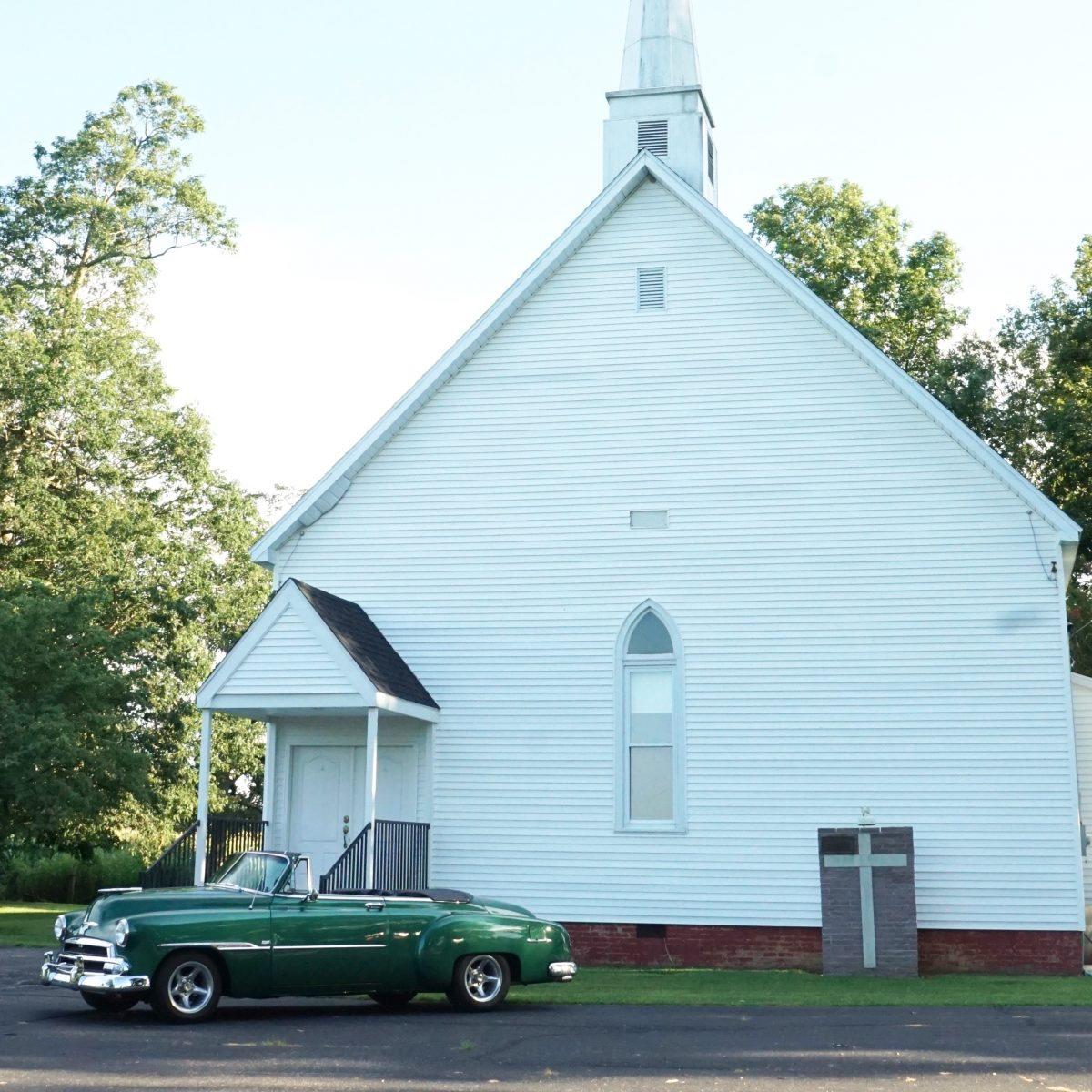 photo of classic car in front of white church