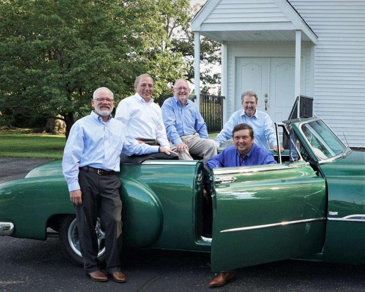 Quartet sitting in classic car
